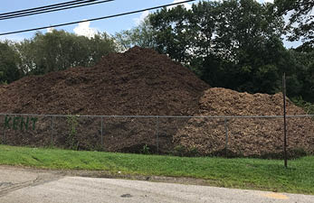 piles of mulch on the side of road